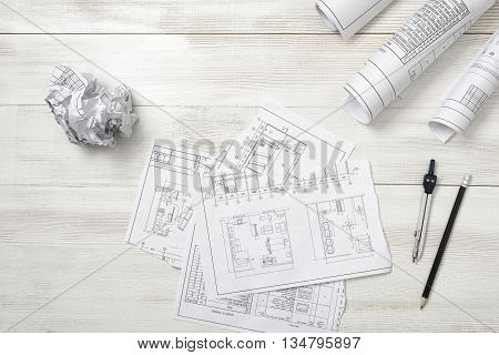 Rolls of drawing sketches, pencil and compass are on wooden surface.. Top view compositin. Workplace of architect or constructor. Engineering work. Construction and architecture. Architect drawing.