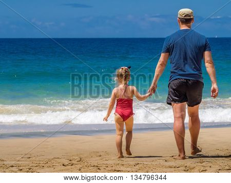 Father and daughter walking together on the beach during summer holidays