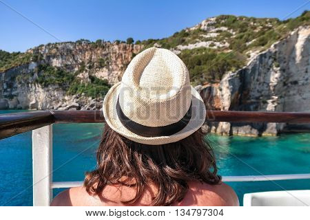 Rear view of young woman enjoying warm sunny day on the cruise, with a white hat. Blue caves in Zakynthos Island
