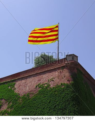Flag of Catalonia fluttering in the wind against clear blue sky. Montjuic castle in Barcelona, Spain