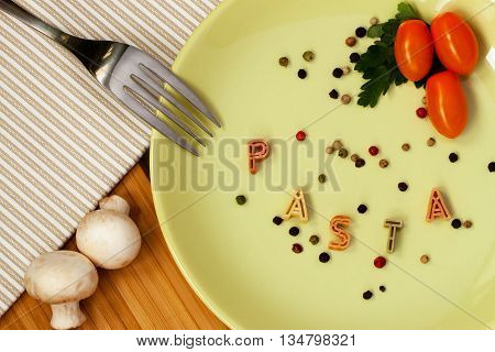 Word Pasta from macaroni Letters witch fresh tomatoes, herbs and mushrooms, background