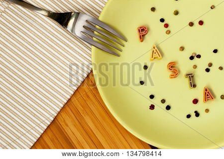 Word pasta made from macaroni Letters on the plate. With your place for the text
