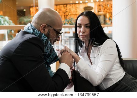 Arab man and the stylish girl sitting and holding hands in an airport lounge