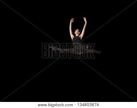 Young pretty ballerina making jump in dance in studio