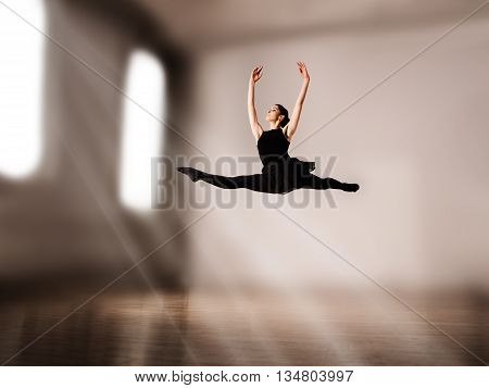 Young pretty ballerina making jump in dance in studio