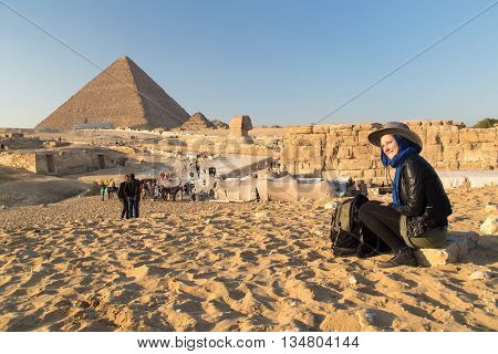 Tourist sitting on the stone at The Giza pyramid complex.