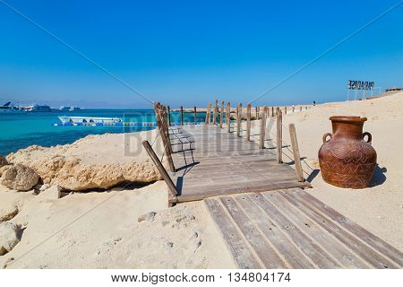 Big decorative vase next to wooden walkway on Paradise Island, Egypt.