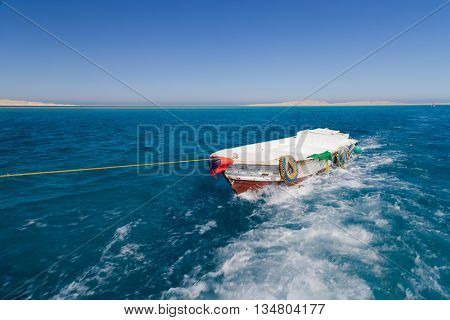Tender boat trails behind snorkelling tourist boat
