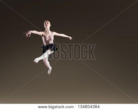 Young beautiful ballerina on dark background in studio