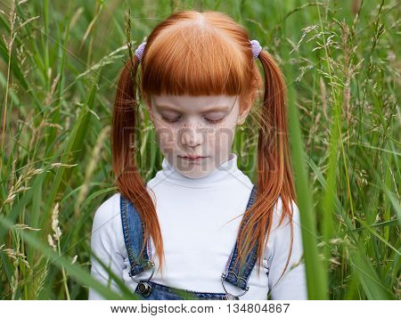 Little sad girl lowered her eyes. Portrait close-up on a background of green grass