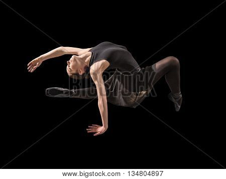 Young woman ballerina stretching warming up in silhouette studio on black background