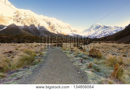 Snow capped mountain partially illuminated during sunrise.