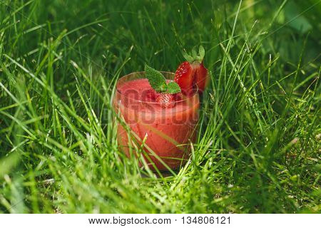 A glass of strawberry smoothie in the grass with mint in the garden