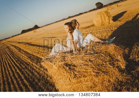 Image of young loving couple sitting on haystack in field
