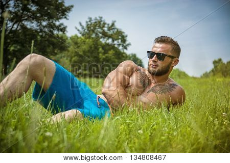 Handsome Muscular Shirtless Hunk Man Outdoor in City Park. Showing Healthy Muscle Body While Looking away, wearing sunglasses