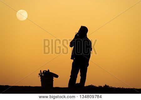 A man is is standing smoking a cigarette silhouetted against a bright orange sunset sky.