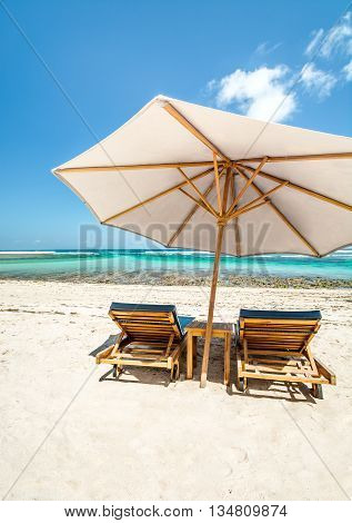 A large Beach Umbrella with lounge chairs on a beautiful beach in Bali.