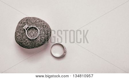 His & hers wedding rings on a white background with her ring in sharp focus and sitting on a textured stone.