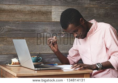 Portrait Of Thoughtful And Concentrated Young African American Copy-writer, Dressed In Pink Shirt, W