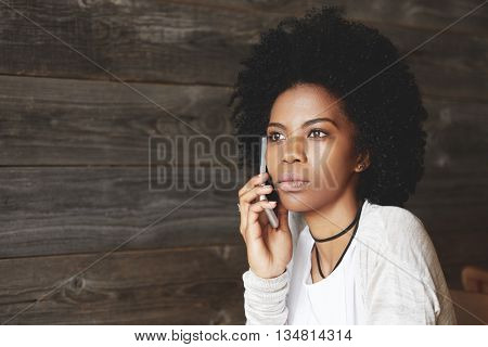 Portrait Of Beautiful African Woman With Afro Hairstyle, Talking On The Mobile Phone With Serious An