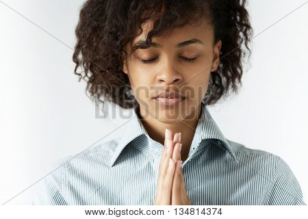 Concept Of Praying And Consideration. Headshot Of Strong Featured African Woman With Shaggy Hair, Cl