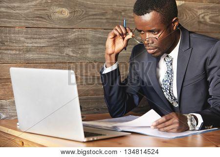 Serious African American Businessman Looking Over His Glasses On Laptop Screen. Focused Gentlemen Ch