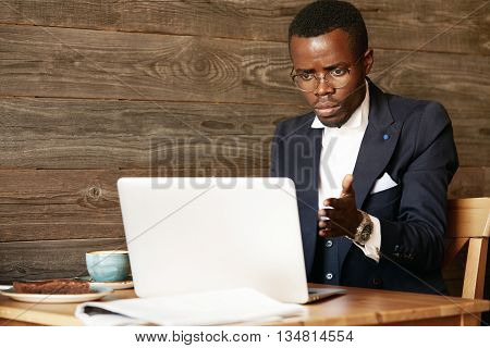Worried Young African Businessman, Sitting In Front Of Laptop, Looking At The Screen With Stressed E
