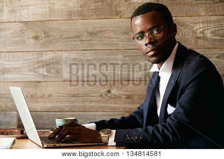 Young Attractive African Man In Rich-looking Suit And Glasses, Keyboarding A Report On Laptop Comput