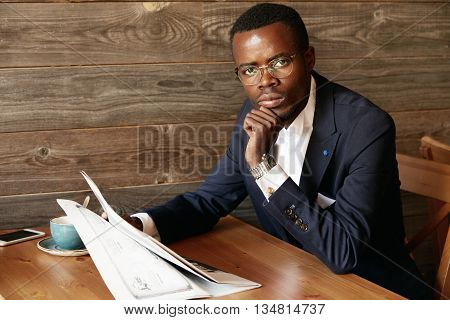 African Office Worker Sitting At The Restaurant, Looking At The Camera With Serious Expression Readi