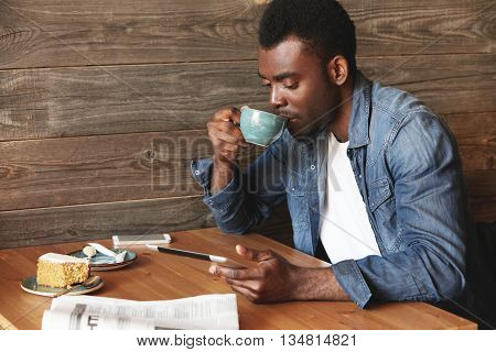 Attractive African American Guy Reading Book On His Tablet And Drinking Tasty Coffee With Honey Dess