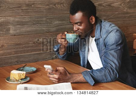 Young And Attractive African Man In Casual Dress Typing Messages In Social Networks And Smiling. He