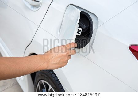 Hand opening the oil filler cap on white car