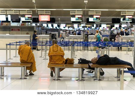Bangkok, Thailand - march 1, 2016: Monks and businessman waiting fly in night quiet airport terminal