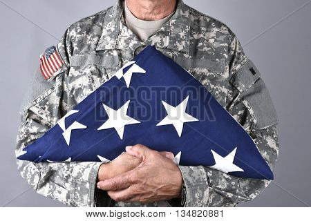 Closeup of an American Soldier in fatigues holding a folded flag in front of his torso. The man is unrecognizable.