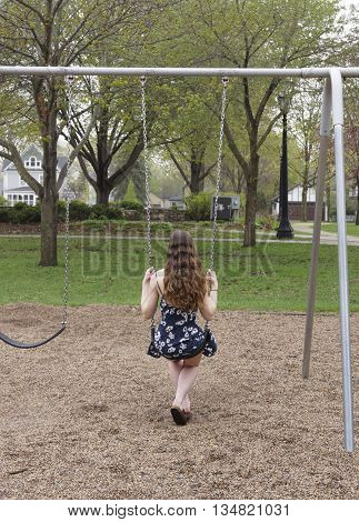 Young woman on a swing in a park