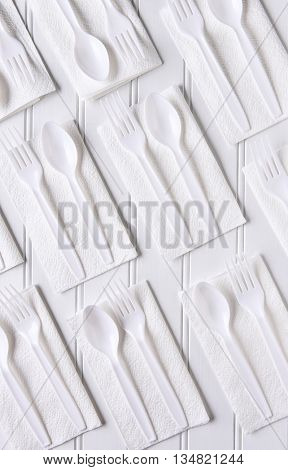 Top view of white napkins with white plastic forks and spoons on a white table. Vertical format.