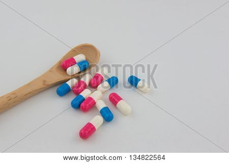 Pills and capsules drug colorful and spoon background