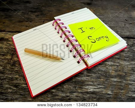 Sorry paper note in note book on wooden table