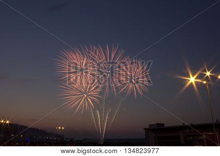 Beautiful colorful holiday fireworks in the evening sky with majestic clouds, long exposure
