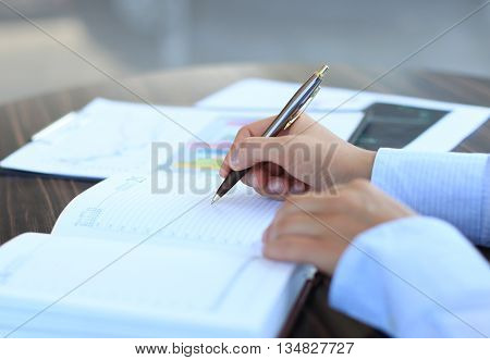 Businesswoman makes a note in her notebook