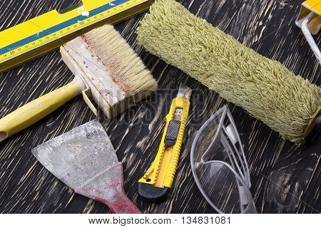 Construction tools: level, roller trowel, glasses, knife and brush on wooden background