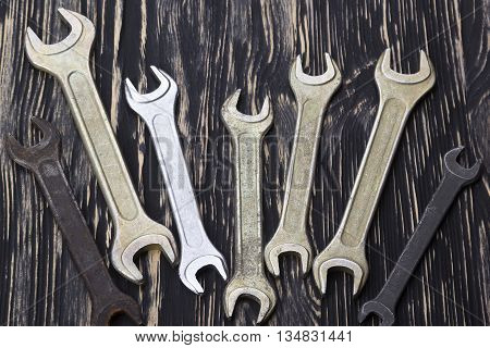 Set of wrenches in several different sizes on natural wooden background.
