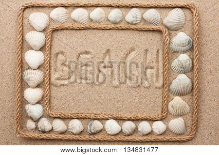 Beautiful frame of rope and seashells on the sand with inscription beach as background