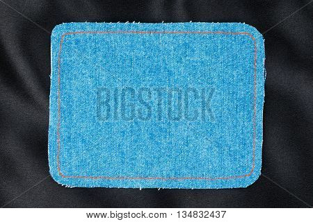 Frame for the text from a blue jeans fabric with the stitched lines of an orange thread on a black silk