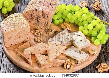 Cheese plate: organic homemade goat cheese with walnuts and spices. Green Grapes and walnuts on an old rustic background studio lights top view close-up