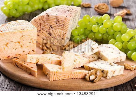 Cheese plate: organic homemade goat cheese with walnuts and spices. Green Grapes and walnuts on an old rustic background studio lights view from above close-up