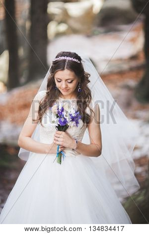 Gorgeous bride in elegant dress holding bouquet and posing near forest.