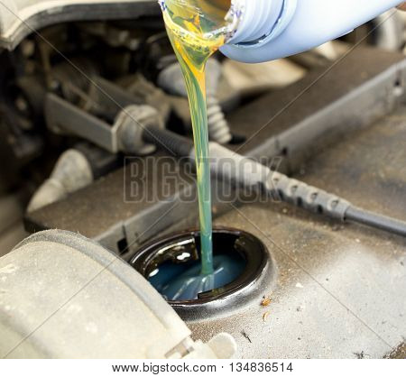 Picture of a Close up of fresh oil being poured into a car dirty and dusty motor
