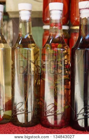 Transparent bottles with an alcohol tincture of herbs and berries