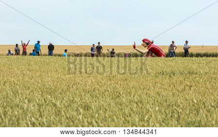 Quievy, France - July 07 2015: Vittel mascot in a wheat field during the passing of the Publicity Caravan on a cobblestone road in the stage 4 of Le Tour de France on July 7 2015 in Quievy France.